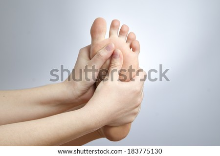 Pain in the foot. Massage of female feet. Pedicures. Studio shot on a gray background. - stock photo
