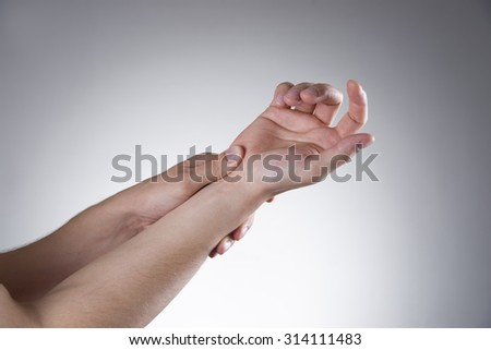 Pain in the joints of the hands on a gray background. Carpal tunnel syndrome. Care of male hands
