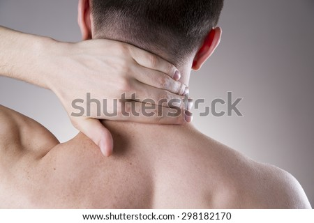 Pain in the neck. Man with backache. Pain in the man's body on a gray background - stock photo