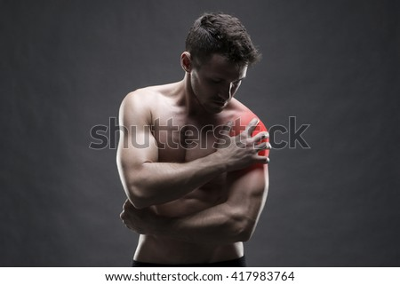 Pain in the shoulder. Muscular male body. Handsome bodybuilder posing on gray background with red dot