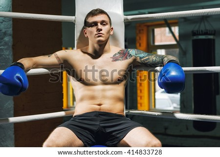 Pain is nothing. Confident young fighter sitting in a corner of a boxing ring. - stock photo