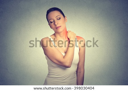 pain. Woman with painful neck shoulder colored in red isolated on gray wall background   - stock photo