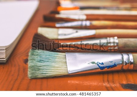 Painbrushes set close-up with an album on a wooden table