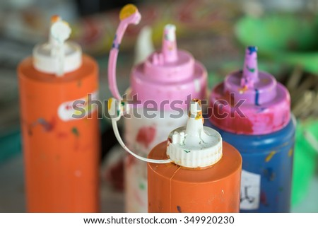 Paint bottles to be squeezed for art and craft education background  - stock photo