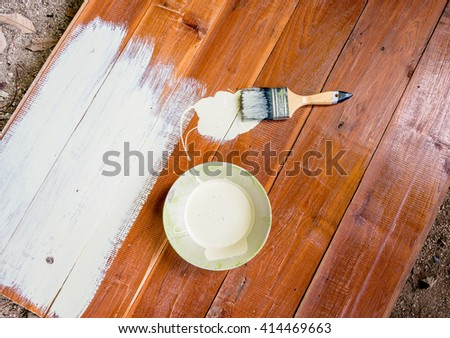 Paint brush and  bowl  of white coating color put on wood board, top view of brush and bowl with white coating color
