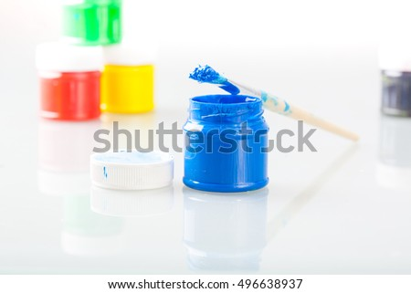 Paint brush and multi colored paint bottles with reflection.