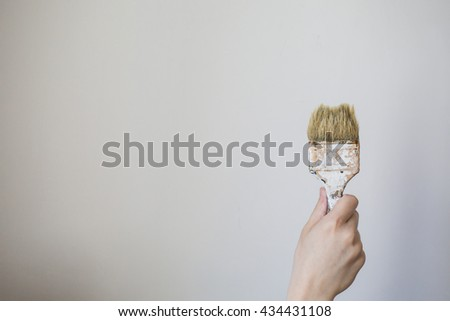 Paint brush in a man's hand on a white background . Process concept. Man painting wall illustration, painting wall image, painting wall concept, Man painting wall website building, painter - stock photo