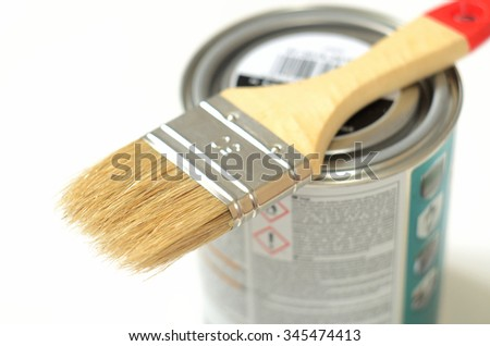 Paint brush lying on the can of paint on a white background