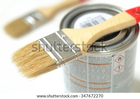 Paint brush lying on the can of paint on a white background - stock photo