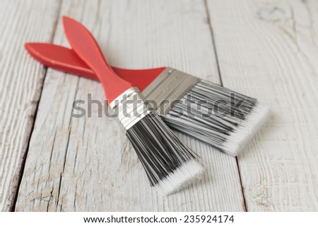 Paint brush on a white wooden board - stock photo