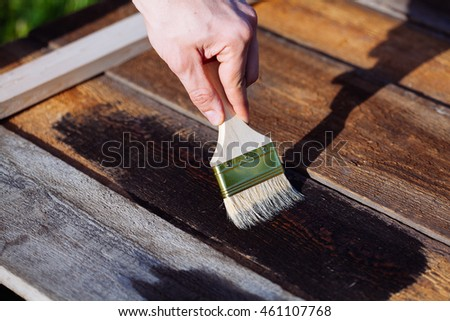 Paint brush on wooden table use for home decorated. House renovation. Half - painted surface. Smear of paint brush