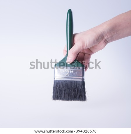 paint brush or paint brush in a hand on background - stock photo