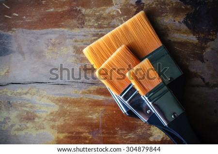 Paint brush or paintbrush resting on the wooden floor. - stock photo
