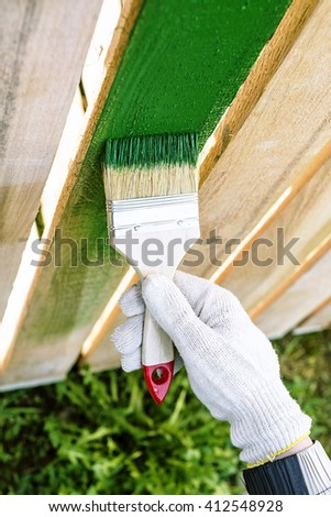 paint brush with wooden handle and dab of green paint , painting wooden furniture, close up, hand in protective glove cotton brush paints the wooden fence, a painter paints construction - stock photo