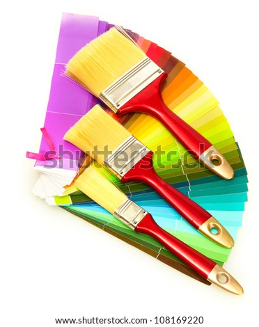 paint brushes and bright palette of colors isolated on white
