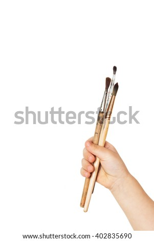 Paint brushes in a child hand isolated on white background. The concept of education drawing, children's art, fresh, creative ideas, etc.