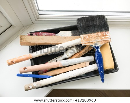 Paint brushes in a tray on a window ledge - stock photo