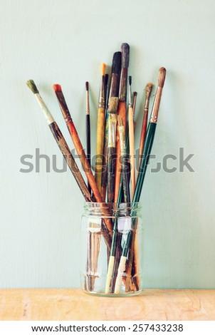paint brushes in jar over wooden aqua blue background. vintage filtered image - stock photo
