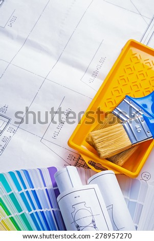 paint brushes in tray rolled blueprints color palette  - stock photo
