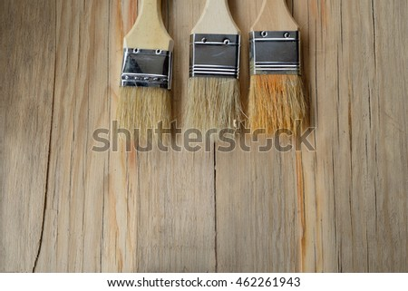 Paint brushes on a wooden table with empty space