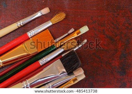 Paint brushes on acrylic paint wooden palette background.