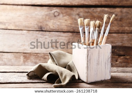 Paint brushes on old wooden background - stock photo