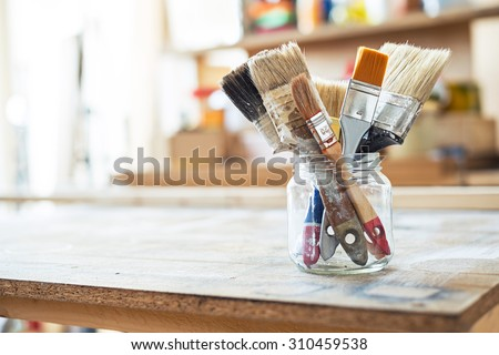 Paint brushes on the table in a workshop. - stock photo
