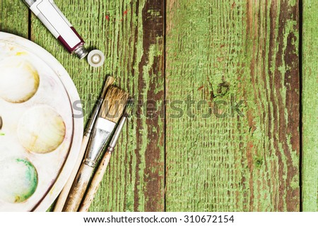 Paint brushes set and a palette with an oil paint tube on a green wooden background - stock photo