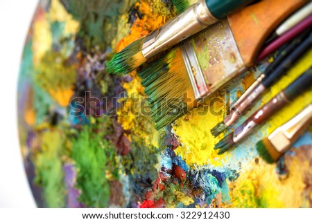 Paint brushes to the painting palette with colors on a white background.