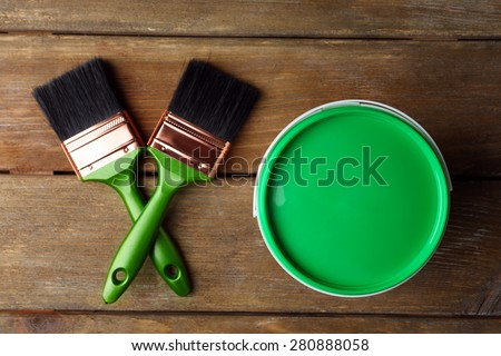 Paint can and paint brushes on wooden background - stock photo