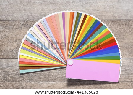 Paint colour palette. Color swatches book on wooden background - stock photo