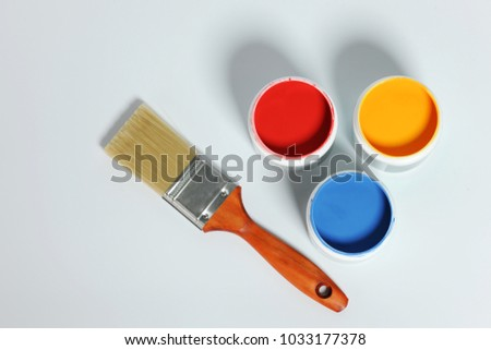 Paint containers and brush isolated on a neutral background