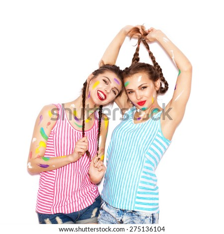 Paint on the face of pretty girl friends having fun. Women smeared in paint. White background not isolated - stock photo