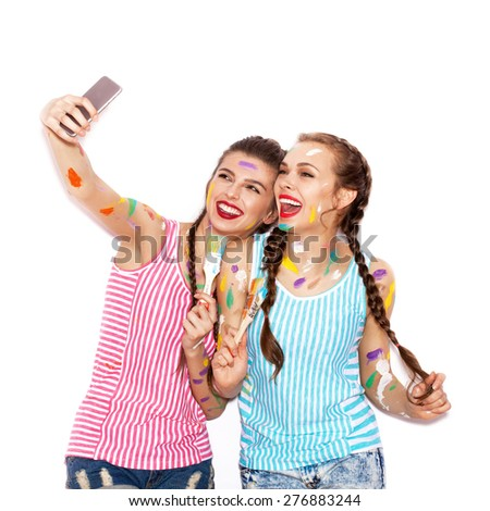 Paint on the face of pretty girl friends having fun. Women with paintbrush taking selfie. White background not isolated - stock photo