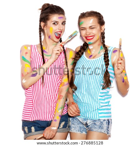 Paint on the face of smiling girl friends having fun. Playful women with paintbrush. White background not isolated - stock photo