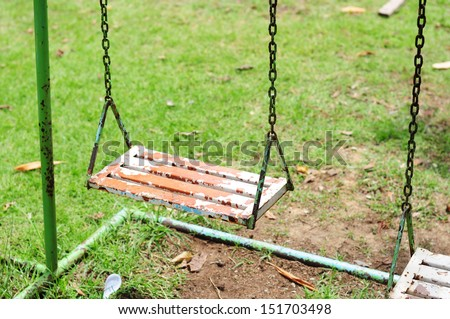 Paint peeling on the swings at the playground. - stock photo