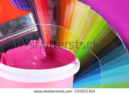 Paint pot, paintbrush and coloured swatches close up - stock photo