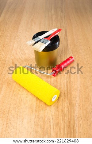 Paint roller, brushes and color bucket on hardwood floor ready for painting. - stock photo