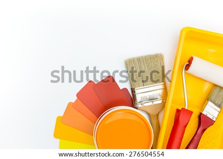 paint roller in tray, brushes, and paint can with color guide - stock photo