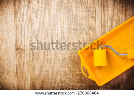 paint roller in tray on wooden board with organized copyspace construction concept  - stock photo