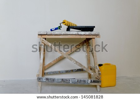 Paint roller, tray and container of solvent standing ready on a wooden trestle to redecorate the interior of a house - stock photo