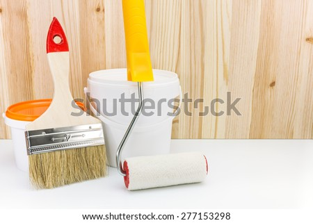 paint roller with brush and paint can against wooden boards - stock photo