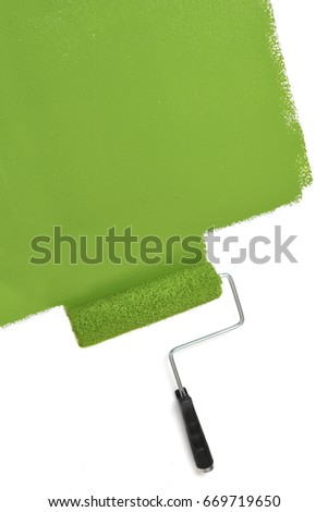 Paint roller with green pigment over white wall