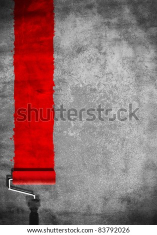 paint roller with red paint on white wall - stock photo