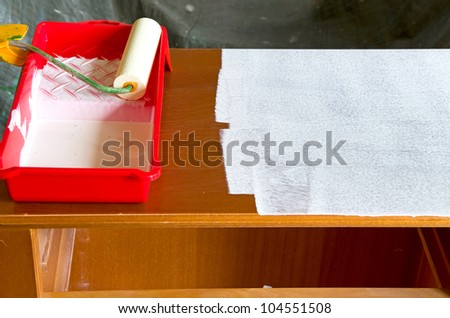 paint roller with white paint and a commode - stock photo