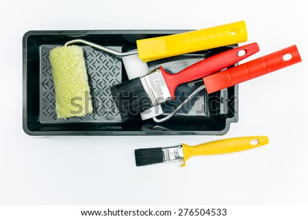 paint rollers and brushes on black tray on white background