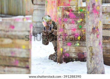 Paintball game in winter. Cool shooter behind fortification. - stock photo