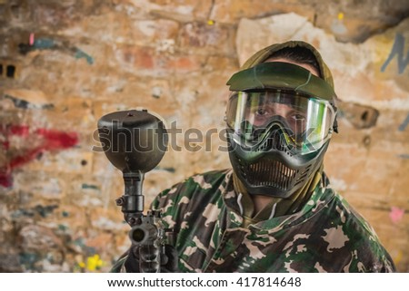 Paintball gamer with gun in camouflage uniform