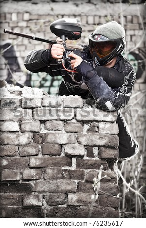 Paintball player aiming with marker in grunge background