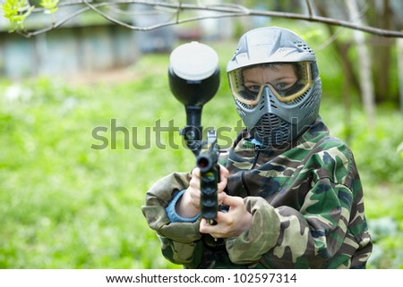 Paintball player in camouflage uniform and protective mask poses, aiming a marker.